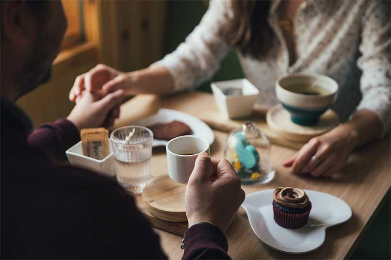 pareja tomados de la mano en una cita desayunando