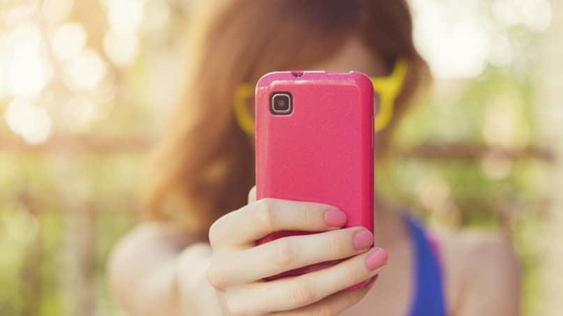 mujer usa un telefono rosa