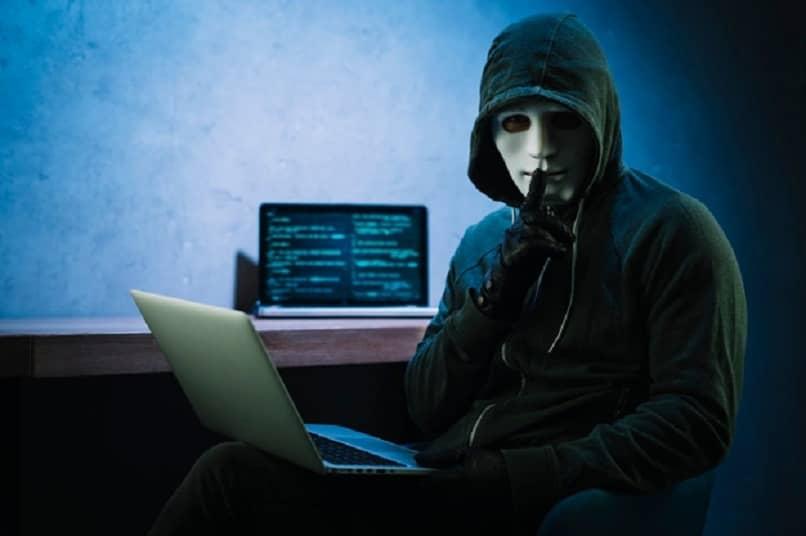 persona con máscara blanca y laptop en mano